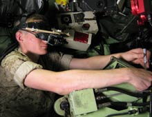 A U.S. Marine technician wears an augmented-reality headset as he carries out a maintenance task inside an armored vehicle.